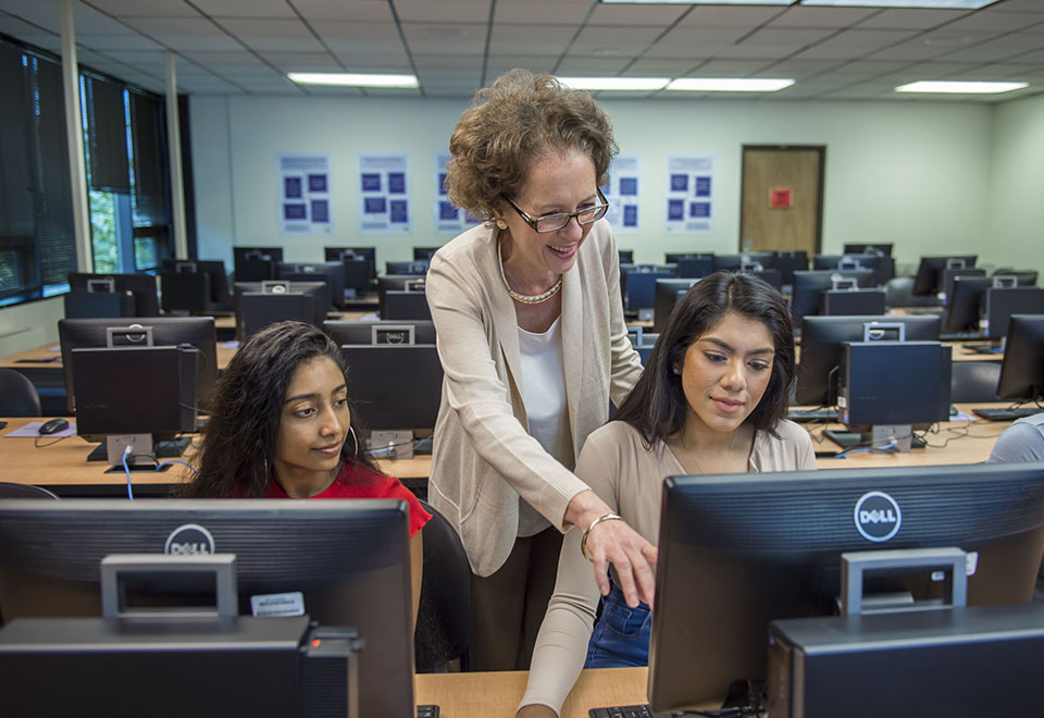 Librarian helps two students at computers in the Rockville library classroom.