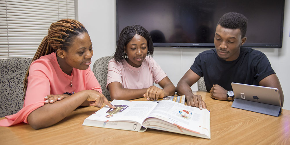 Three students look at a textbook in a study room at the TP/SS library.