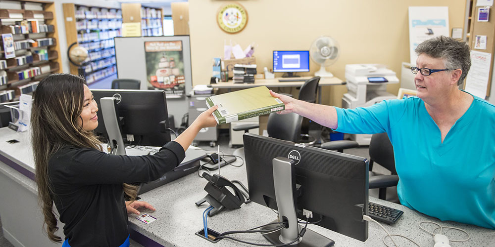 Library employee hands student textbook at library service desk.