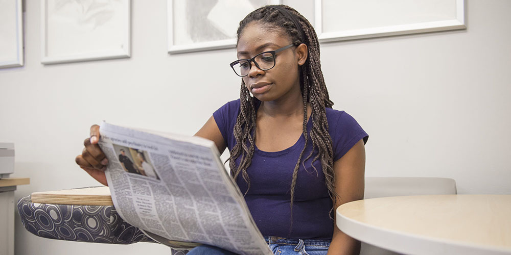 Student reads newspaper at Germantown Campus library.